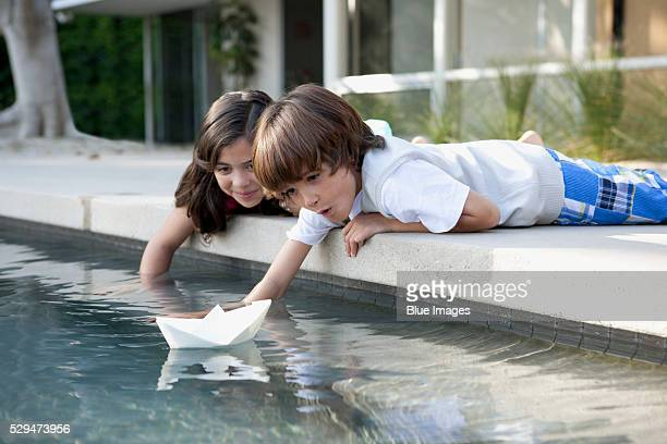 Brother and sister floating paper boat on swimming pool