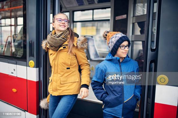 brother and sister getting off the tram - czech republic stock pictures, royalty-free photos & images