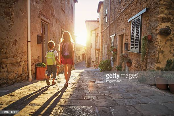 Brother and sister going to school in little town street.