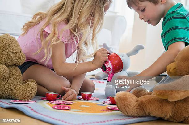 Brother and sister having a tea party together