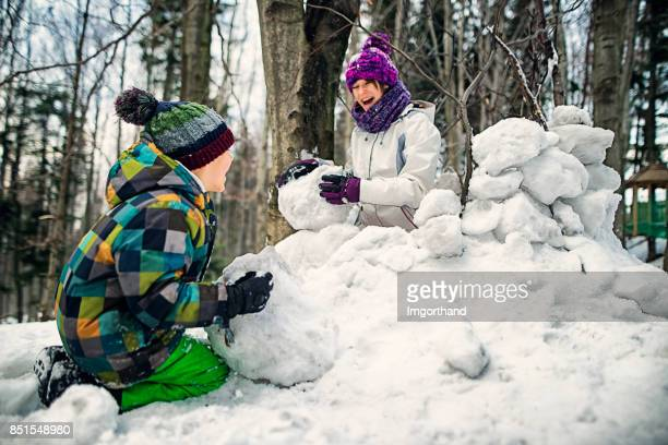 Brother and sister having fun building a snow fortress in forest