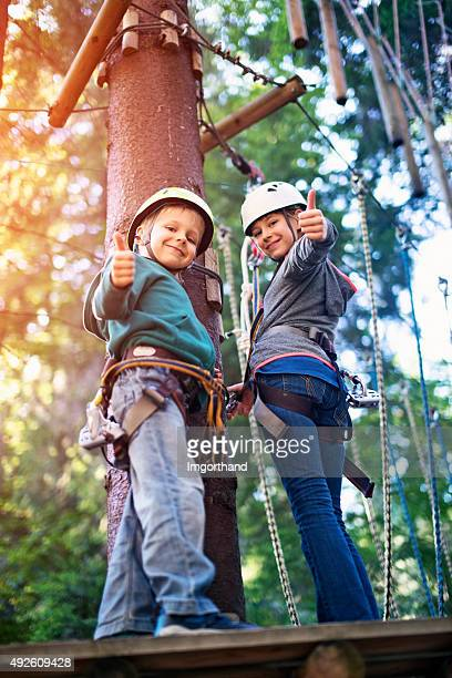 Brother and sister having fun in ropes course adventure park