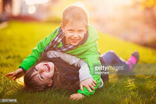 Brother and sister having fun on garden lawn