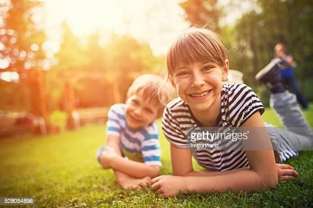 Hermano y hermana divirtiéndose en césped del jardín