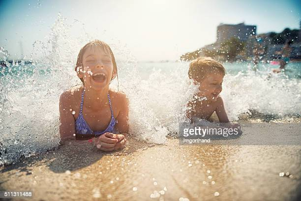 brother and sister having fun splashed in sea - candid beach stock photos and pictures