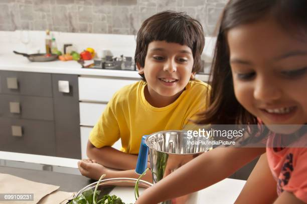 Brother and sister having fun together in kitchen
