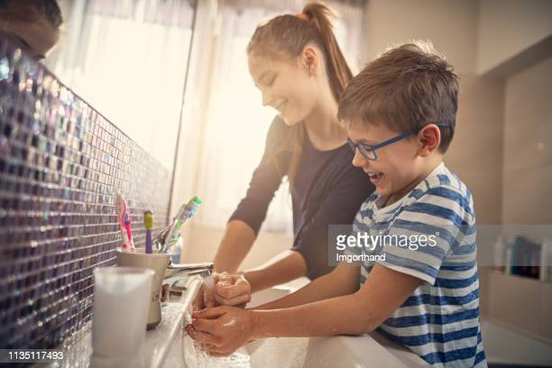 brother and sister having fun washing hands - handwashing stock pictures, royalty-free photos & images