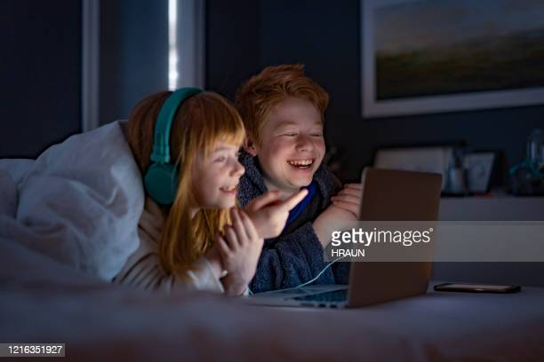 brother and sister having fun watching on computer - surfing the net stock pictures, royalty-free photos & images