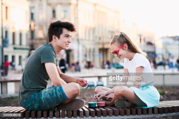 brother and sister having ice cream while sitting in city - broer stockfoto's en -beelden
