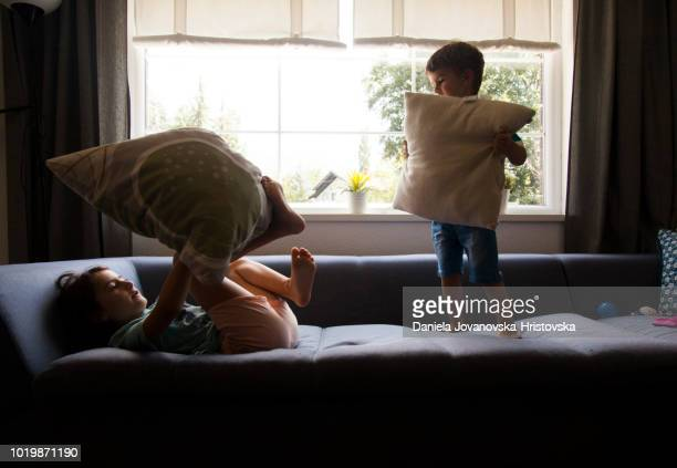 brother and sister having pillow fight - girl fight stock photos and pictures