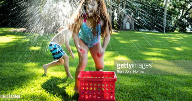 Brother and sister having playful water fight outdoors