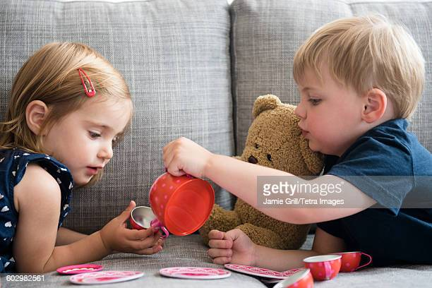 brother (2-3) and sister (2-3) having tea party with teddy bear - tea party stock pictures, royalty-free photos & images