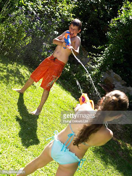 brother and sister (9-12) having water fight in garden - 12 13 jaar stockfoto's en -beelden