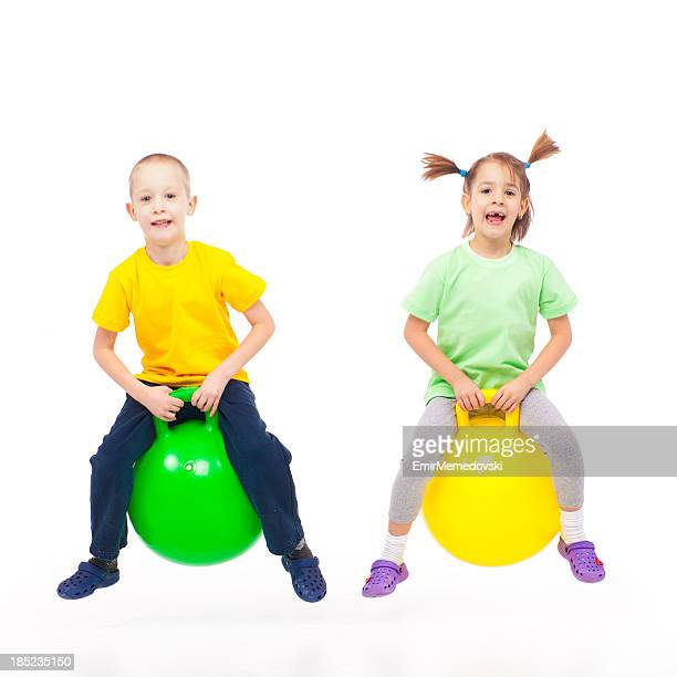 brother and sister heaving fun with bouncing ball