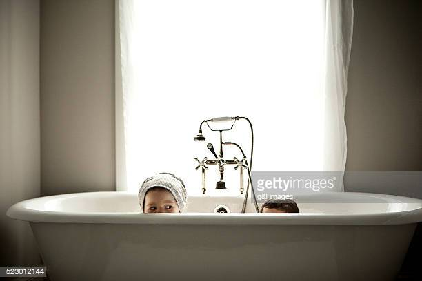 Brother and sister (5-6) hiding in bathtub