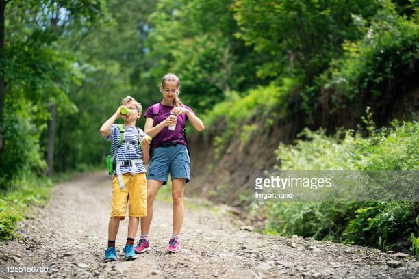 brother and sister hikers drinking from reusable water bottles. - reusable stock pictures, royalty-free photos & images