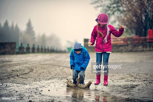 Brother and sister hikers playing in a early spring puddle