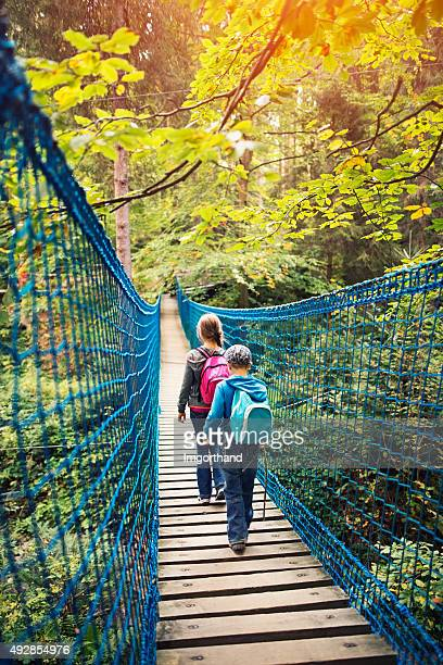 Brother and sister hikers walking on suspension bridge in forest
