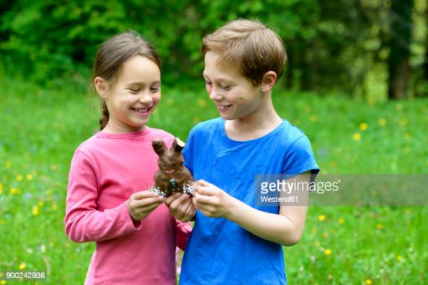 Brother and sister holding chocolate Easter bunny
