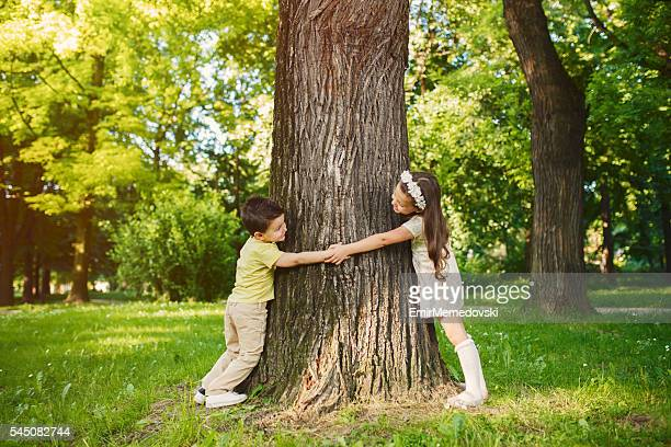 Brother and sister holding hands and hugging tree.