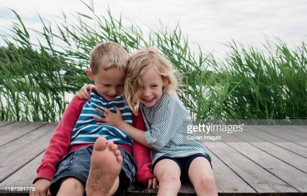 brother and sister hugging and laughing at the beach in summer - nur kinder stock-fotos und bilder