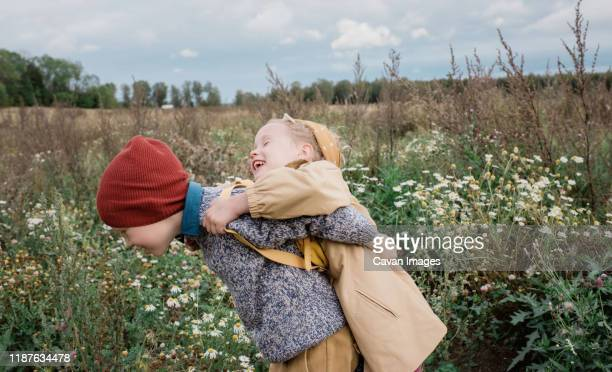 brother and sister hugging and laughing whilst playing outside - zus stockfoto's en -beelden