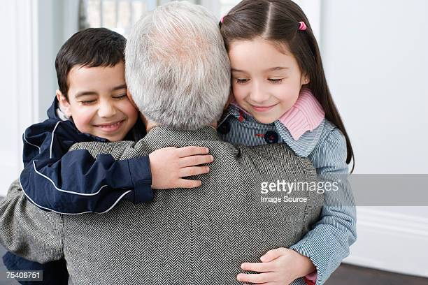brother and sister hugging grandfather - coat stock pictures, royalty-free photos & images