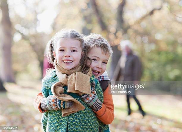 brother and sister hugging outdoors - brother stock pictures, royalty-free photos & images