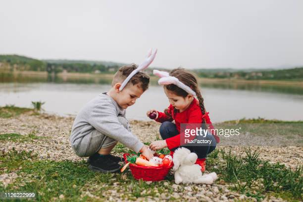 brother and sister hunting for eggs on easter - easter religious stock pictures, royalty-free photos & images