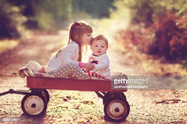 brother and sister in a wagon on a sunlit road