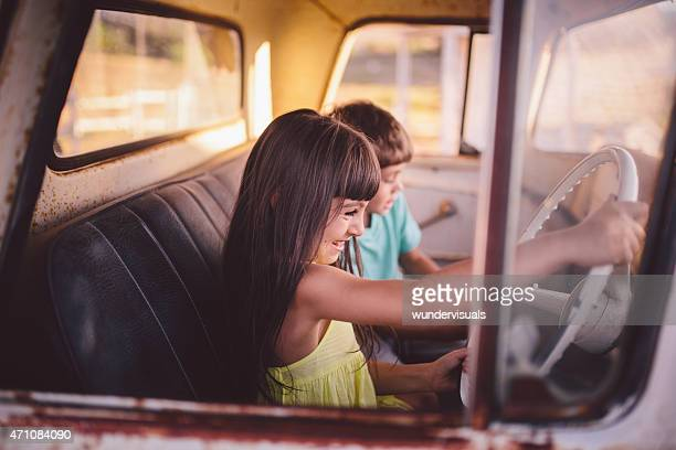 Brother and sister in an old vehicle pretending to drive