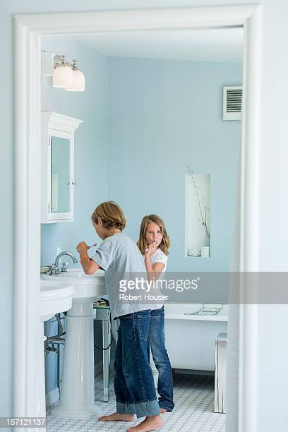 Brother and sister in bathroom mirror