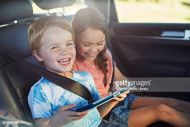 Brother and sister in car using tablet