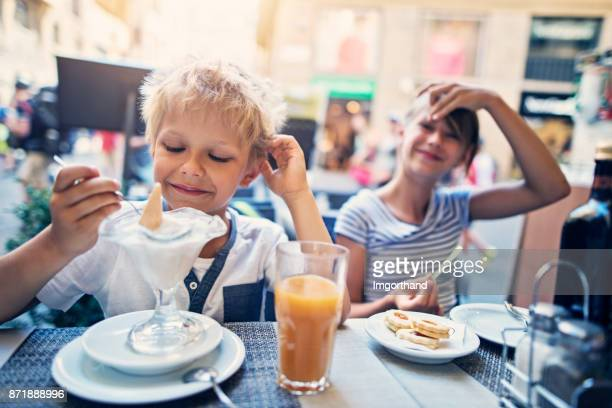 brother and sister in florence ice cream parlour - florence italy stock photos and pictures