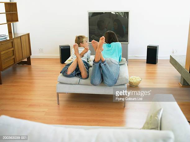 Brother (7-9) and sister (14-16) in front of television