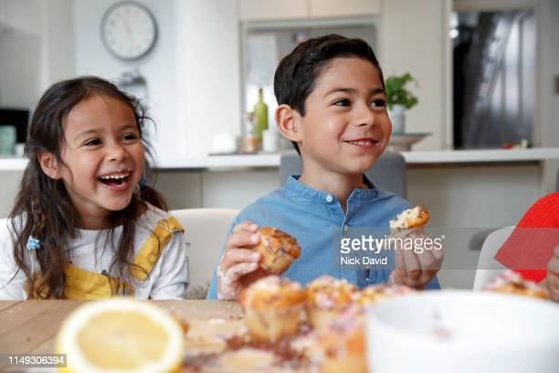 brother and sister in kitchen eating cakes - children only stock pictures, royalty-free photos & images