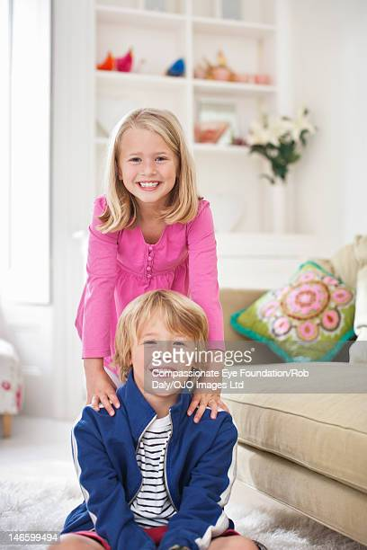 Brother and sister in living room, smiling
