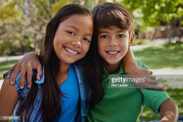 Brother and sister in park, hugging, portrait