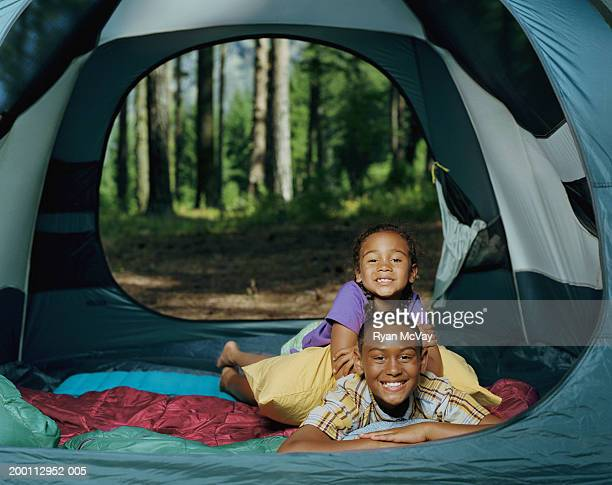 Brother and sister (6-11) in tent, portrait