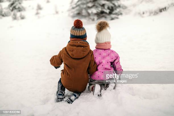 brother and sister in winter idyll - knit hat stock pictures, royalty-free photos & images