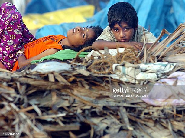 Brother and sister Indian tsunami survivors rest amongs debris of their house in Nochikuppam near Madras 13 January 2005 India has said some 10327...