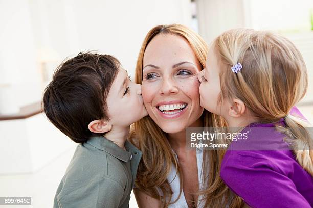brother and sister kissing her mother