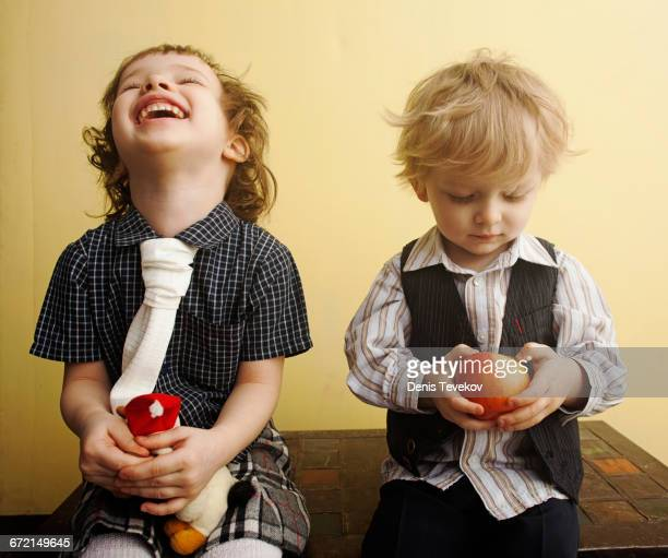 Brother and sister laughing and holding apple on table