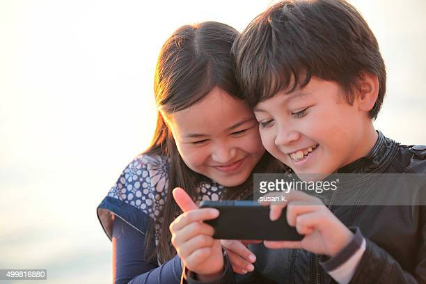 Brother and sister laughing happily looking at a smart phone.