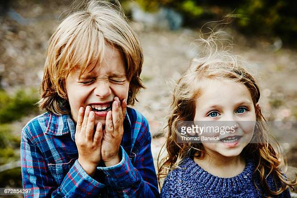 Brother and sister laughing while camping