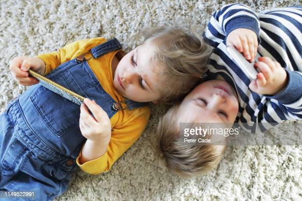 brother and sister laying down looking at phones - iphone stock pictures, royalty-free photos & images
