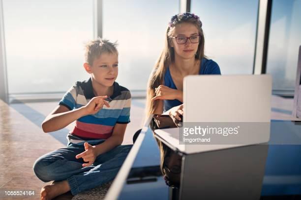 broer en zus leren van gebarentaal online - gebaren stockfoto's en -beelden
