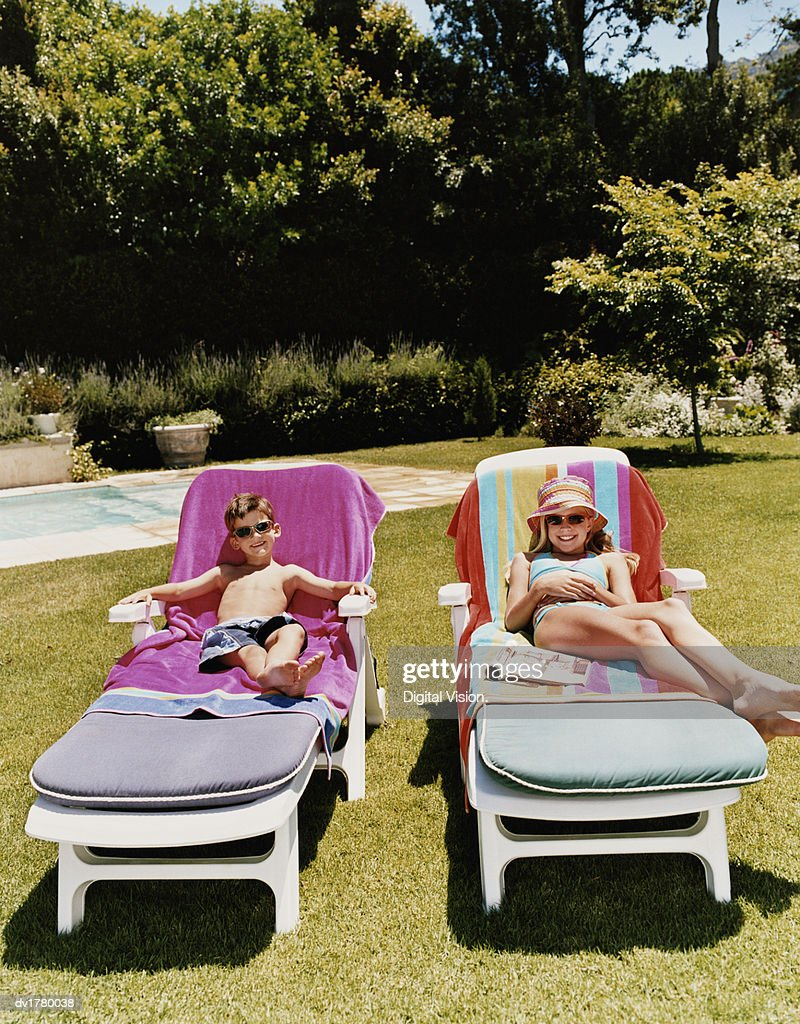 Brother And Sister Lie On Deck Chairs Sunbathing : Stock Photo