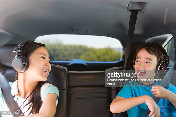 brother and sister listening to headphones in car - vehicle interior stock pictures, royalty-free photos & images