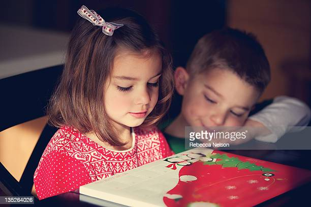 brother and sister looking at advent calendar - avvento foto e immagini stock
